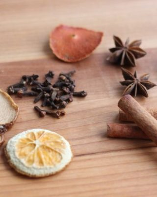 dried apple and orange slices with cloves, cinnamon, star anise on wooden countertop