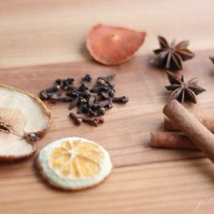 dry apple and orange slices with whole cloves, cinnamon, star anise on wooden coutertop