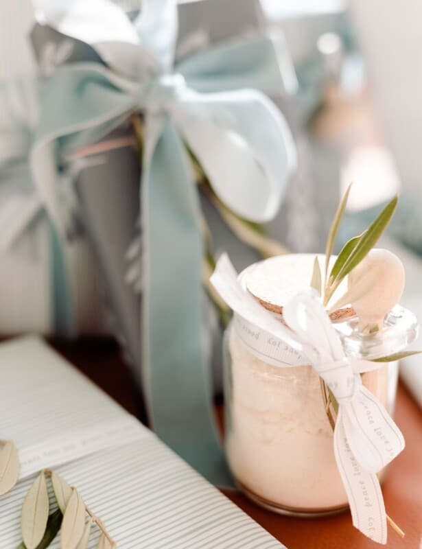 A clear glass jar of mint milk bath recipe under a tree with blue and wrapped gifts.