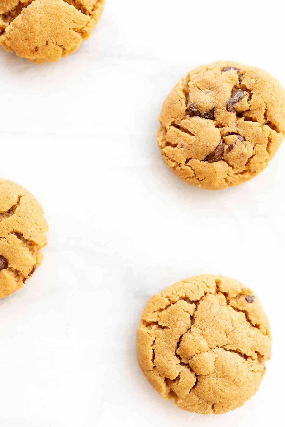 gluten free peanut butter chocolate chip cookies scattered on marble counter