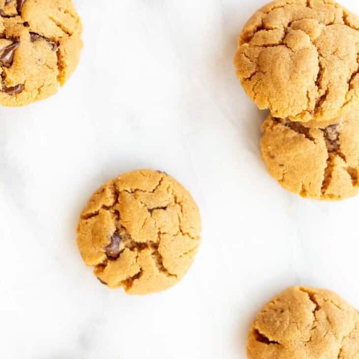 flourless peanut butter chocolate chip cookies scattered on marble counter