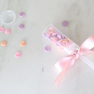 colorful sprinkles scattered and plastic confetti popper with a ribbon