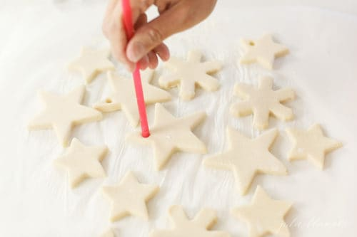 poking hole with a straw into salt dough ornaments
