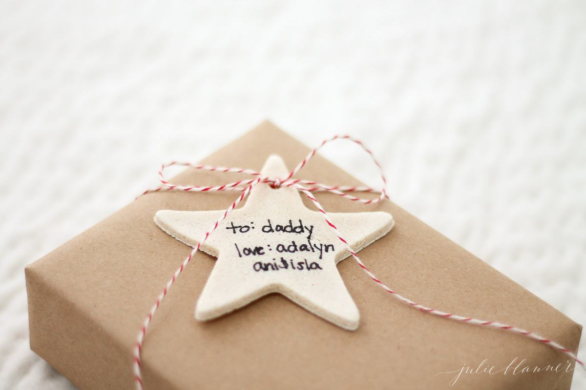 salt dough ornament gift tag in the shape of a star, tied on gift wrapped in brown paper.