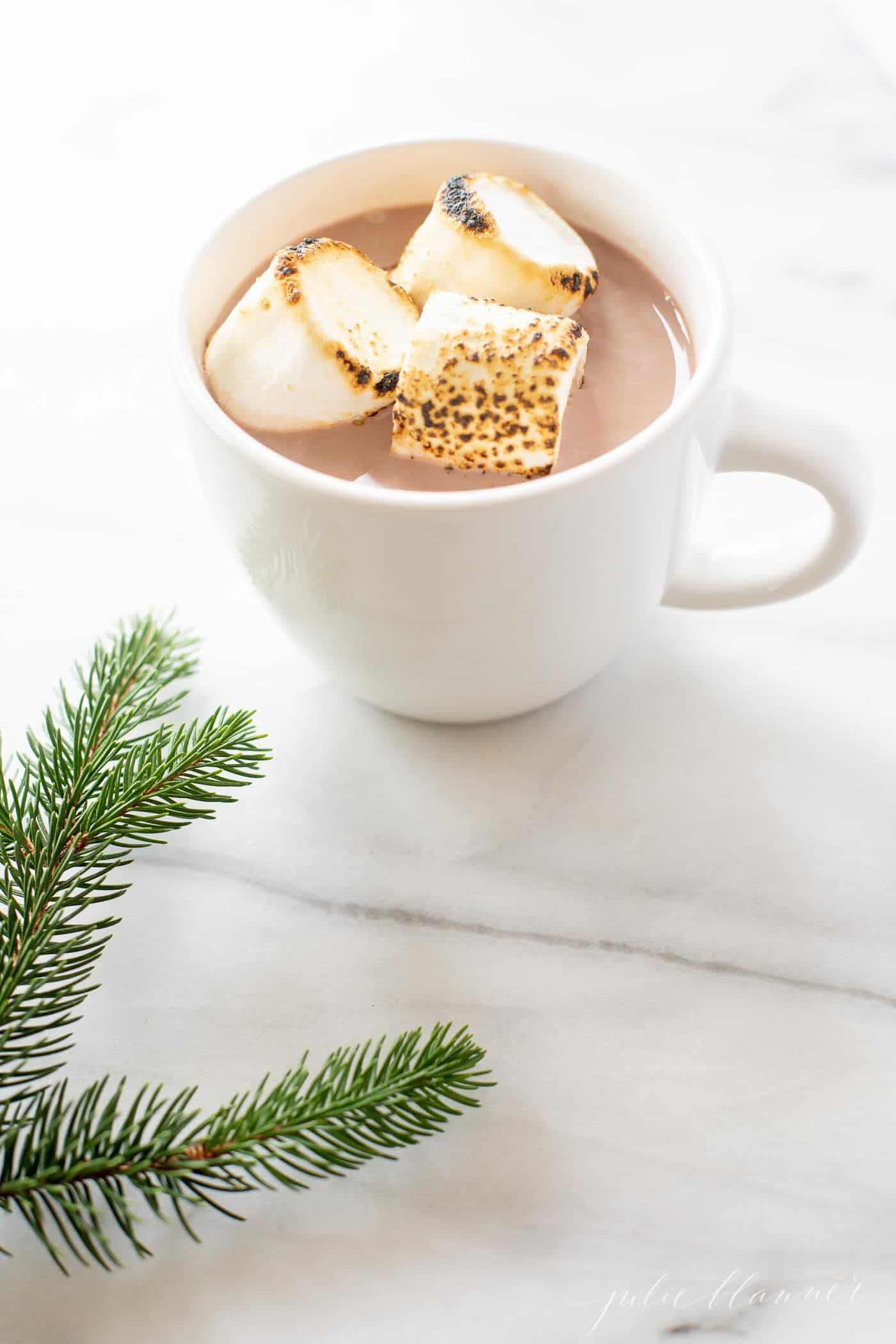A white mug full of spiked hot chocolate Christmas cocktail, topped with toasted marshmallows.