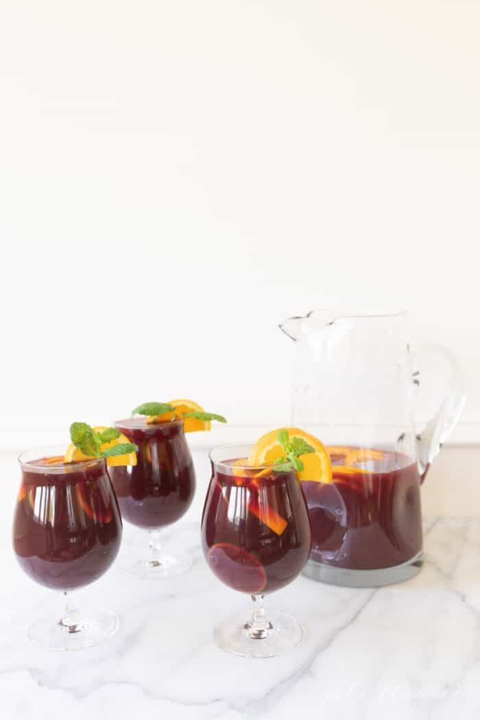 A clear glass pitcher and three glasses full of sangria for Christmas.