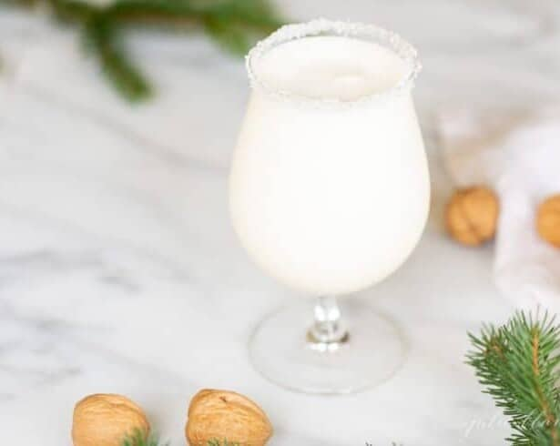 A clear stemmed glass filled with a white Christmas cocktail, topped with a sugared rim, hazelnuts and greenery to the side.