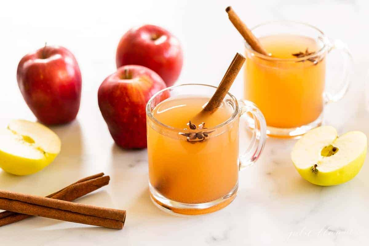 Two clear glass mugs of apple cider Thanksgiving drinks, apples and cinnamon sticks in background.