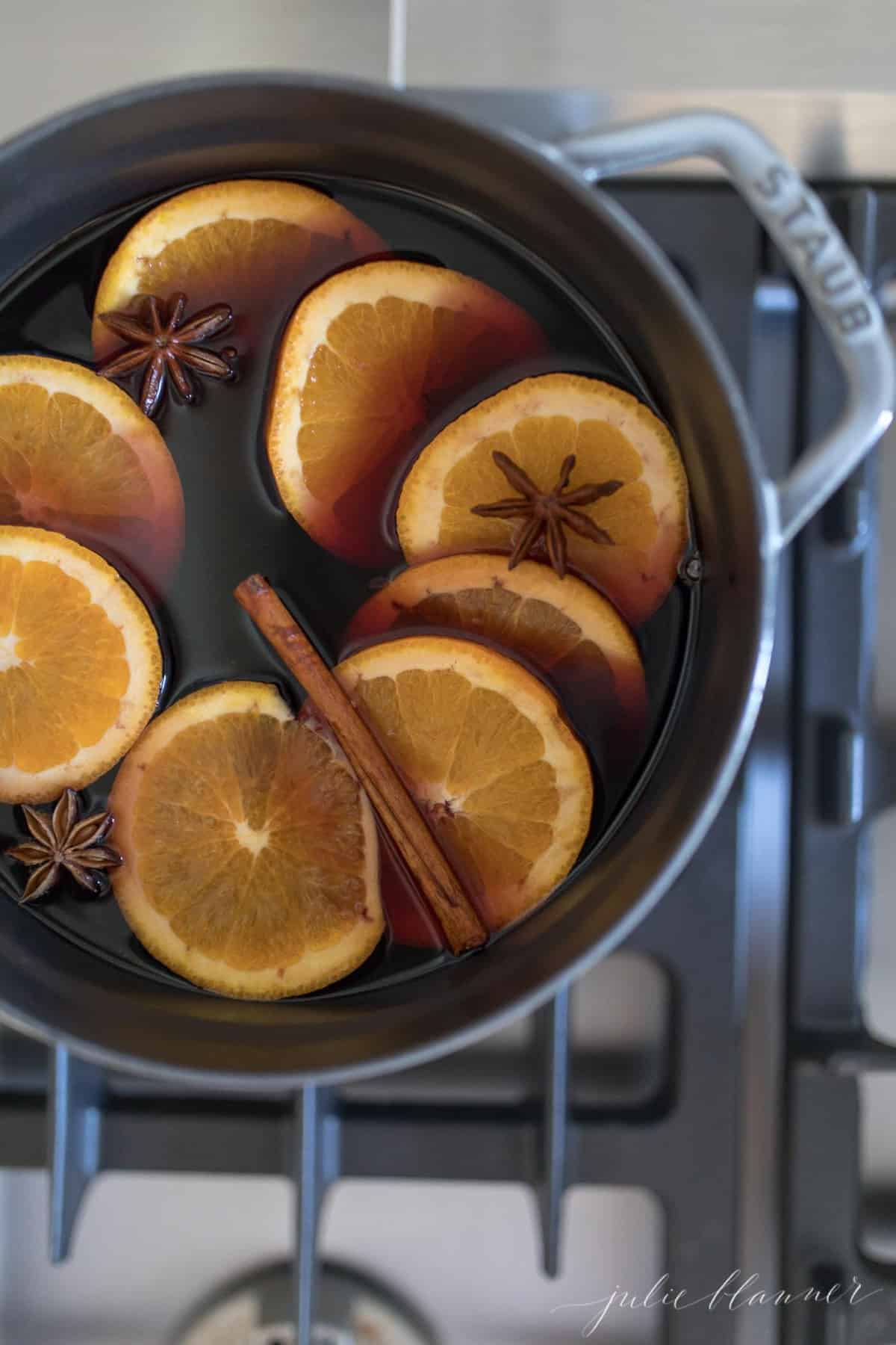 A gray pot on the stove filled with a mulled Thanksgiving drink recipe