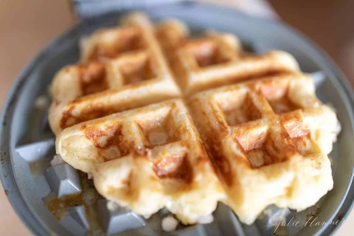 Inside a wafflemaker, an authentic belgian waffle is cooked.