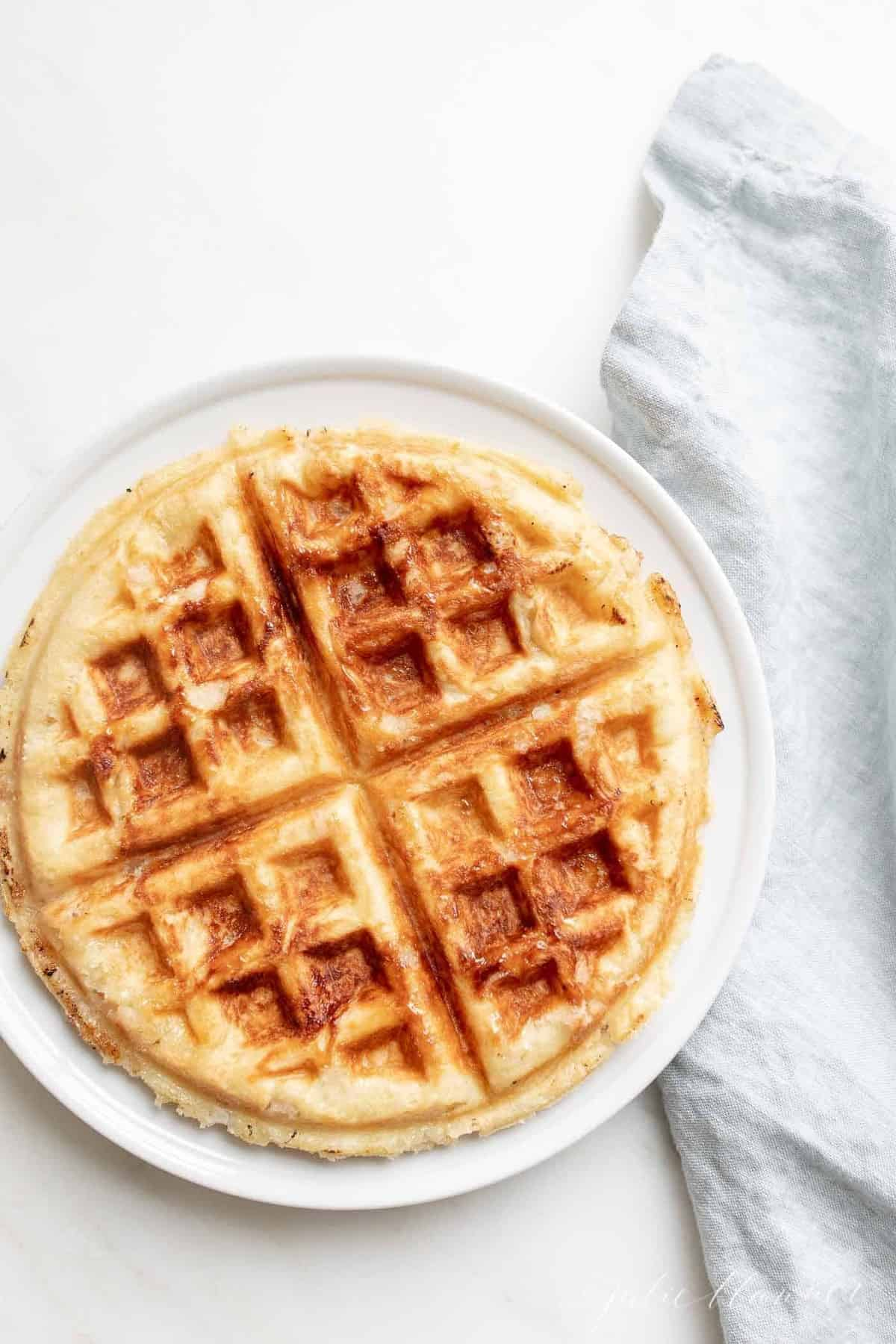 An authentic Belgian waffle on a white plate, blue linen napkin to the side.