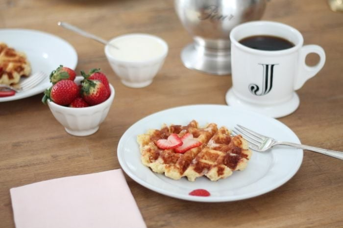 authentic belgian waffle recipe with sliced strawberries on white plate with coffee and strawberries