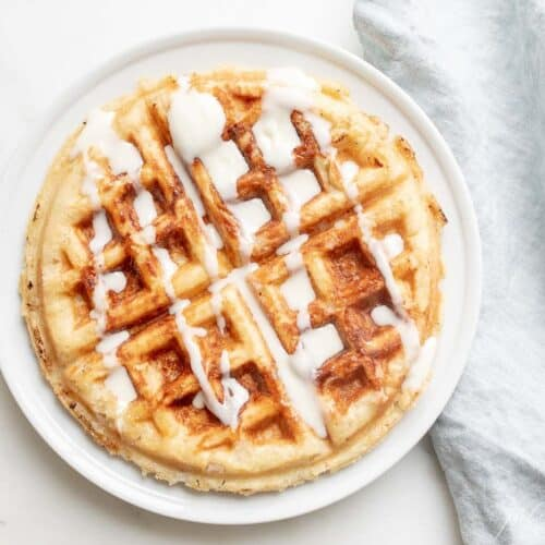 A Belgian waffle topped with creme fraiche drizzle, on a white plate with a linen napkin to the side.
