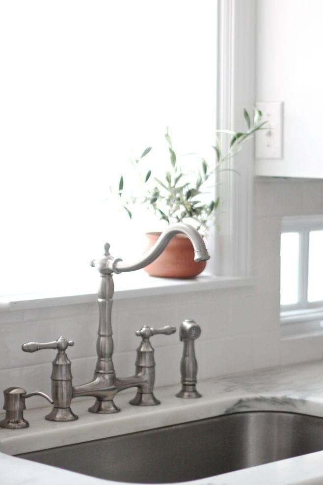 A beautiful bridge faucet adds character to this timeless all white kitchen