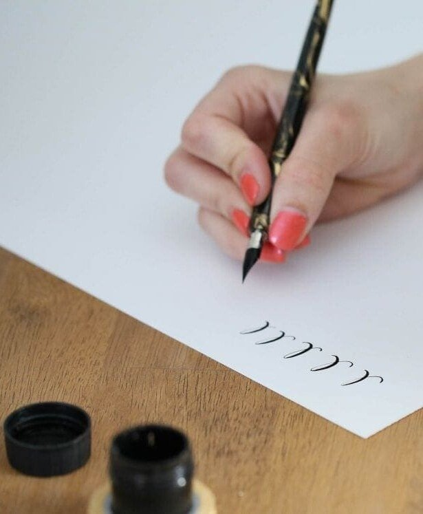 A woman practicing the calligraphy alphabet.