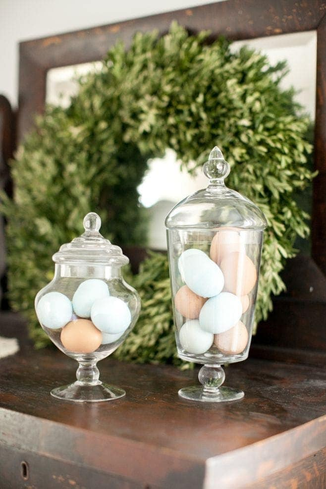 Two glass apothecary jars filled with wooden pastel eggs.