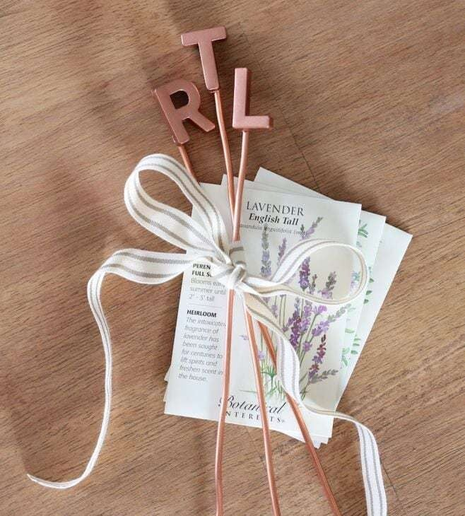 Three copper letter markers tied together with a ribbon and plant seeds as well.