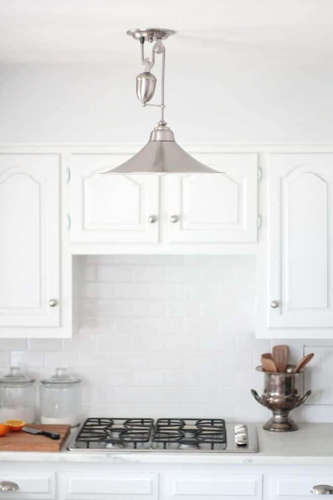 A silver light fixture in a white low budget kitchen renovation.