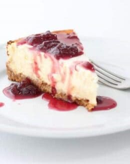 A slice of cheesecake on a white plate, topped with a strawberry cheesecake topping.