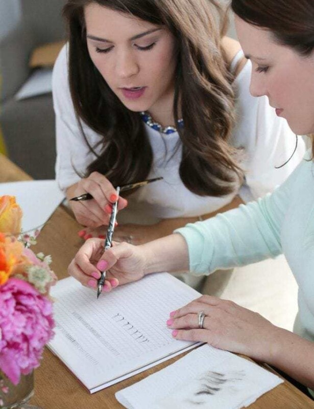 A bouquet of flowers in a vase on a table with two people practicing calligraphy.
