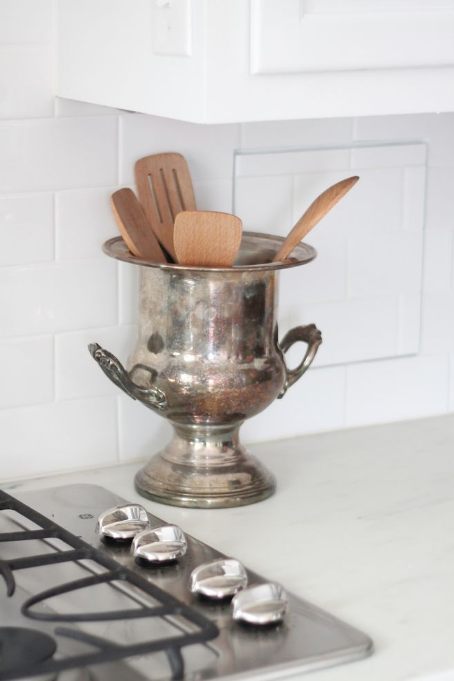 a vintage champagne holder doubles as a utensil holder in this functional kitchen from julieblanner.com
