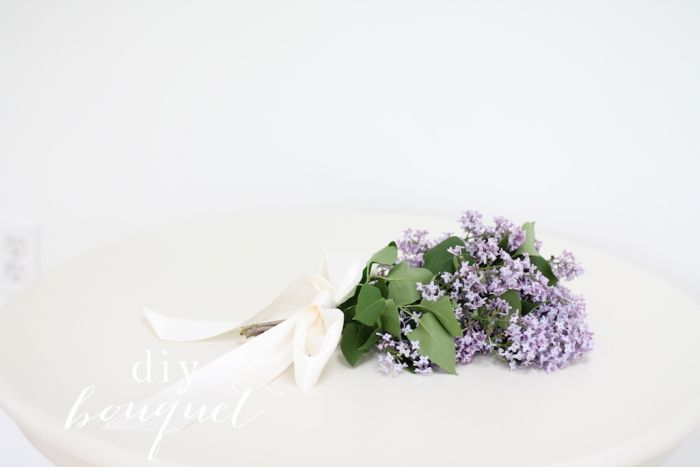 White background with a hand tied purple lilac bouquet.