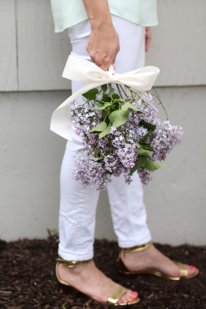 A woman holding a hand held bouquet of fresh cut common purple lilac blooms.