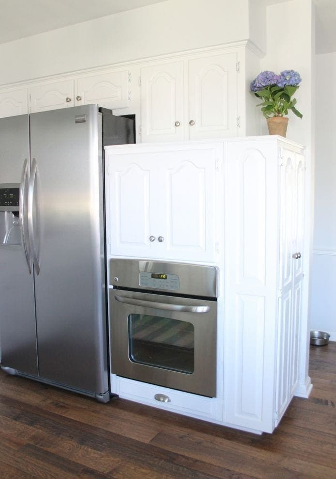 A white themed kitchen with stainless steel appliances, and a cabinet with a toaster and microwave in it.