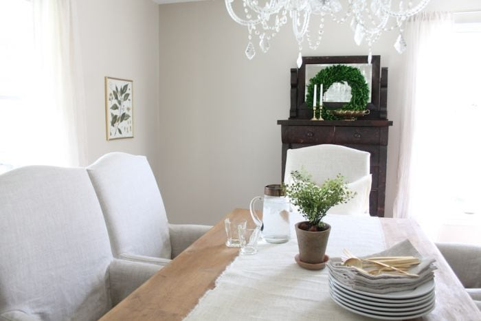 A dining room painted in Sherwin Williams Accessible beige, with upholstered white chairs and a wood table.