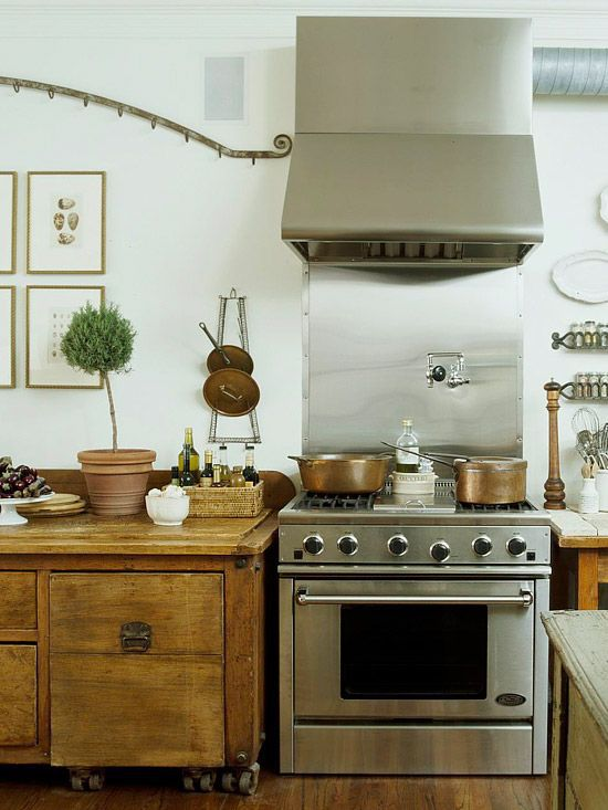 Better Homes & Gardens kitchen filled with copper, found furniture for cabinetry & all beautifully styled with a topiary & vintage art
