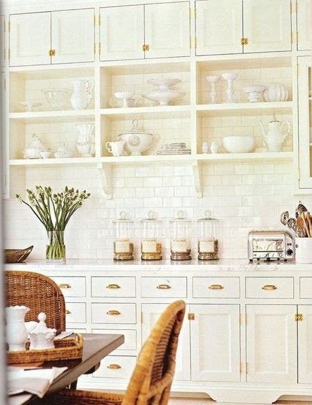 Classic cream colored kitchen cabinetry with brass hardware. Great mix of open shelving with cabinets.
