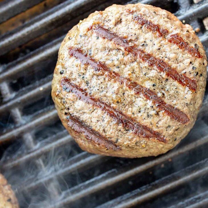 A perfectly charred grilled burger on a smoking gas grill grate