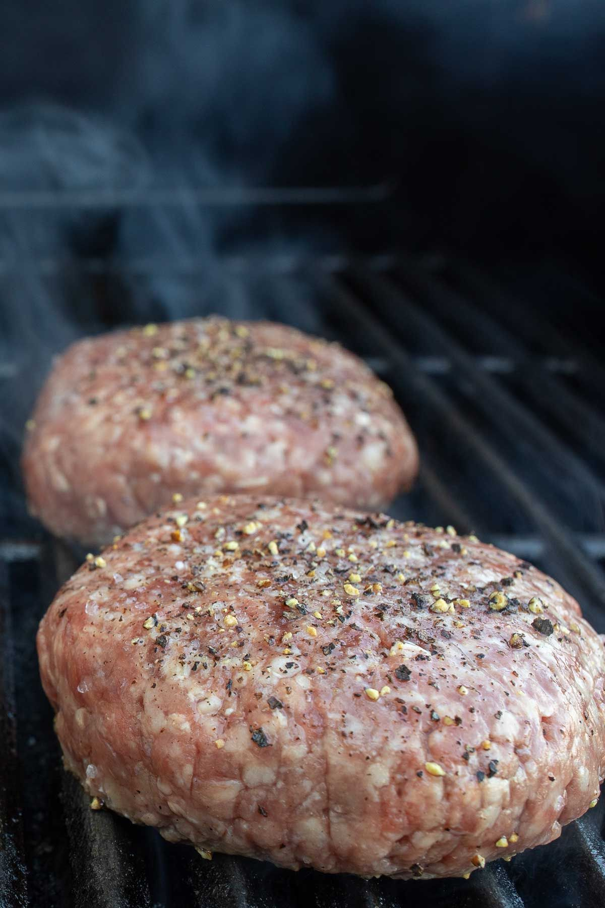 Grilled burgers on a gas grill grate, smoke rising.