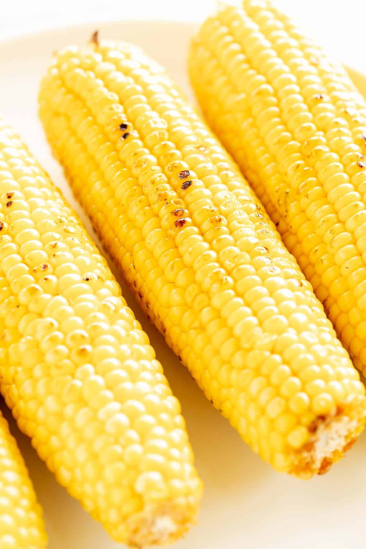 Ears of grilled corn on the cob on a white plate.
