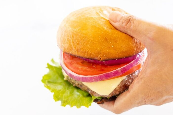 hands holding A hamburger stacked with lettuce, tomato, cheese and red onion.