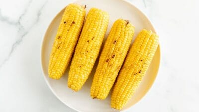 A white plate full of grilled sweet corn on a marble surface.