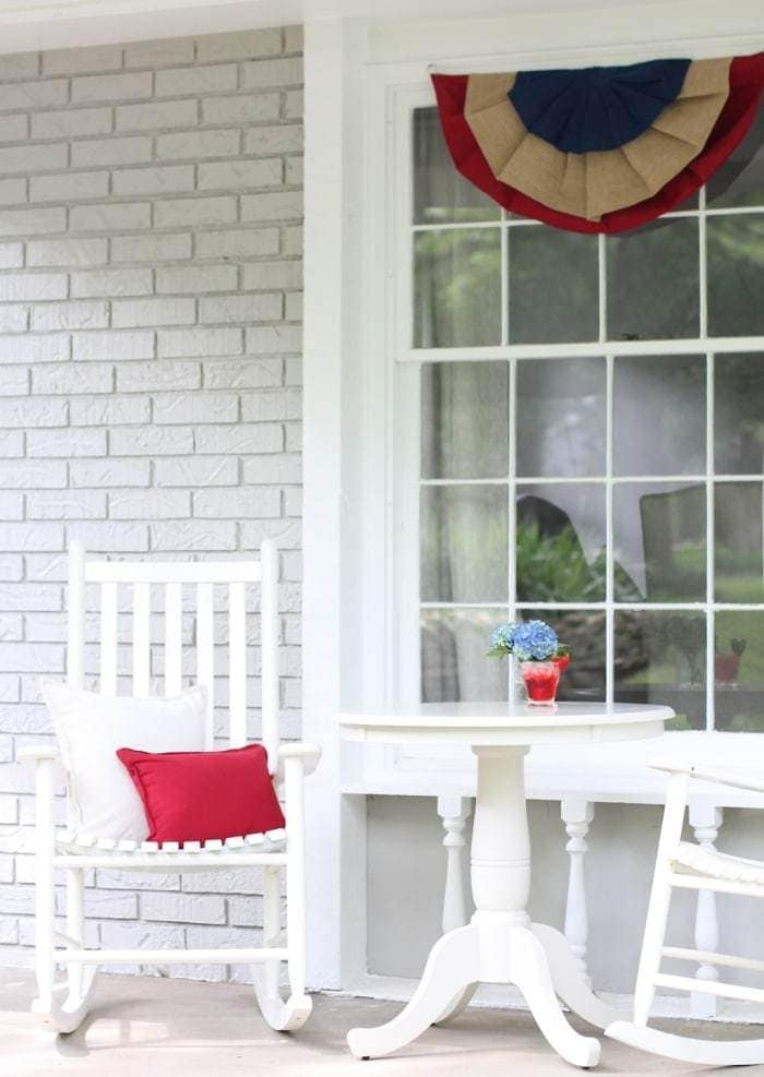 A window decoration, with a layered red, blue, and burlap decoration hanging from the top of the window. White chairs and a white table sit below.