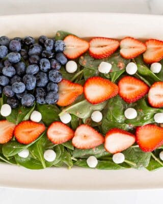 A red white and blue salad shaped into an American flag, on a white platter.