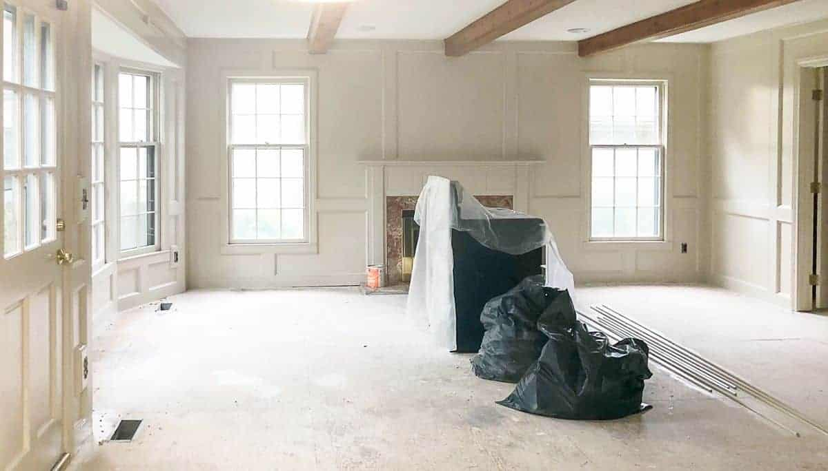 A large living room mid-renovation, walls painted in Sherwin Williams Accessible Beige.