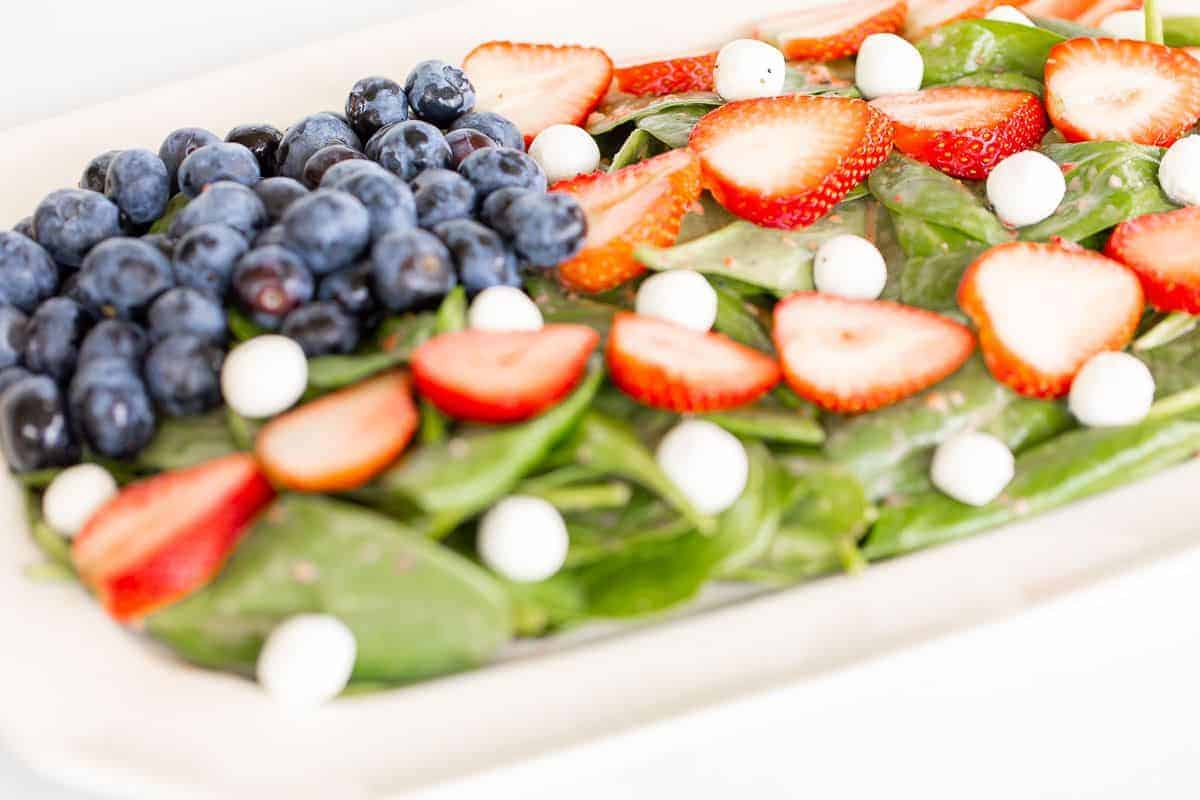 A 4th of july salad shaped into an American flag on a white rectangular platter.