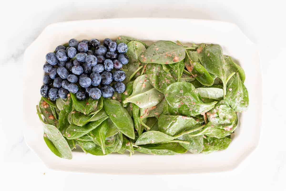 A blueberry and strawberry spinach salad on a rectangular platter, in the process of being made.