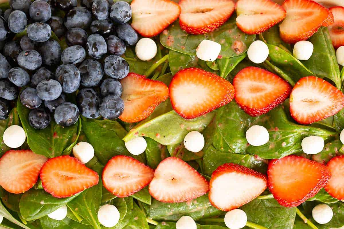 A blueberry strawberry salad on a bed of spinach, shaped into a flag.