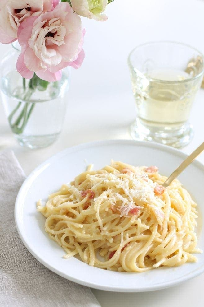 easy pasta carbonara recipe on white plate with glass of white wine and pink flowers in vase