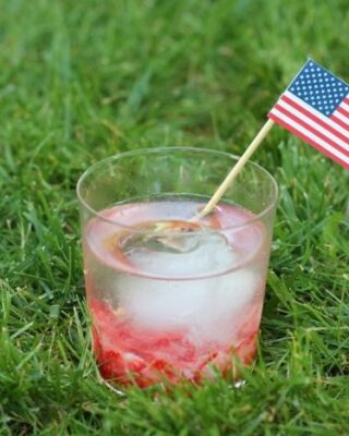 A Caipirinha Cocktail in a clear glass with a paper drink flags in the grass