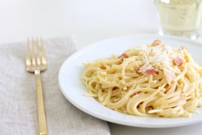 spaghetti alla carbonara on white plate with gold fork and glass of white wine for brunch