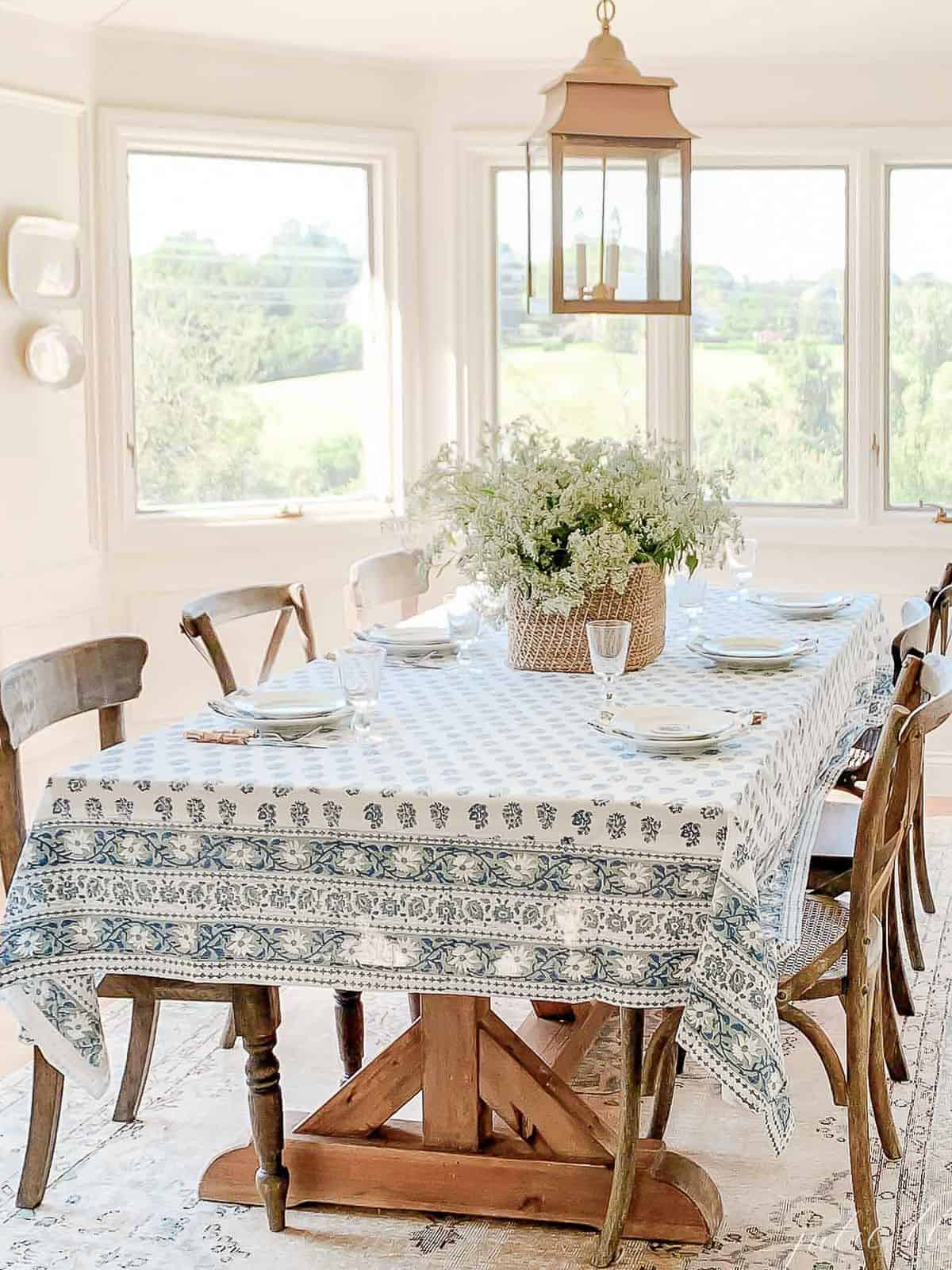 A white dining room with a brass lantern over the table, white platters on the wall hung with plate hangers in the background.