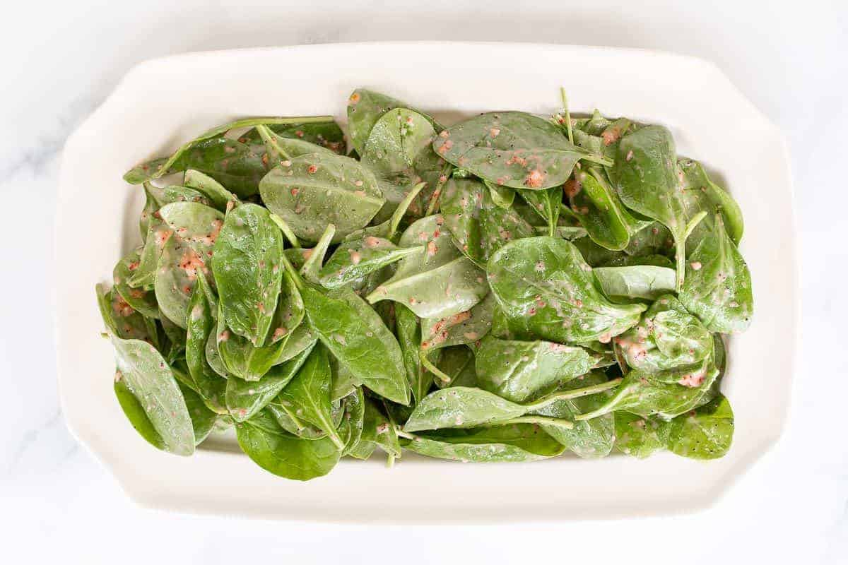 A strawberry spinach salad on a rectangular platter, in the process of being made.