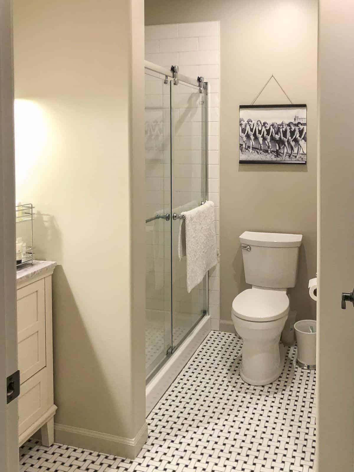 SW Accessible Beige in a small bathroom with a black and white vintage tile floor.