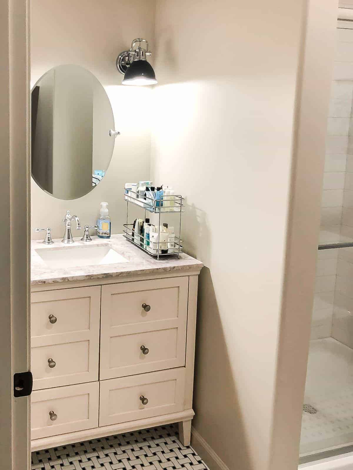 A small bathroom painted in sherwin williams accessible beige, with a cream vanity and oval mirror.