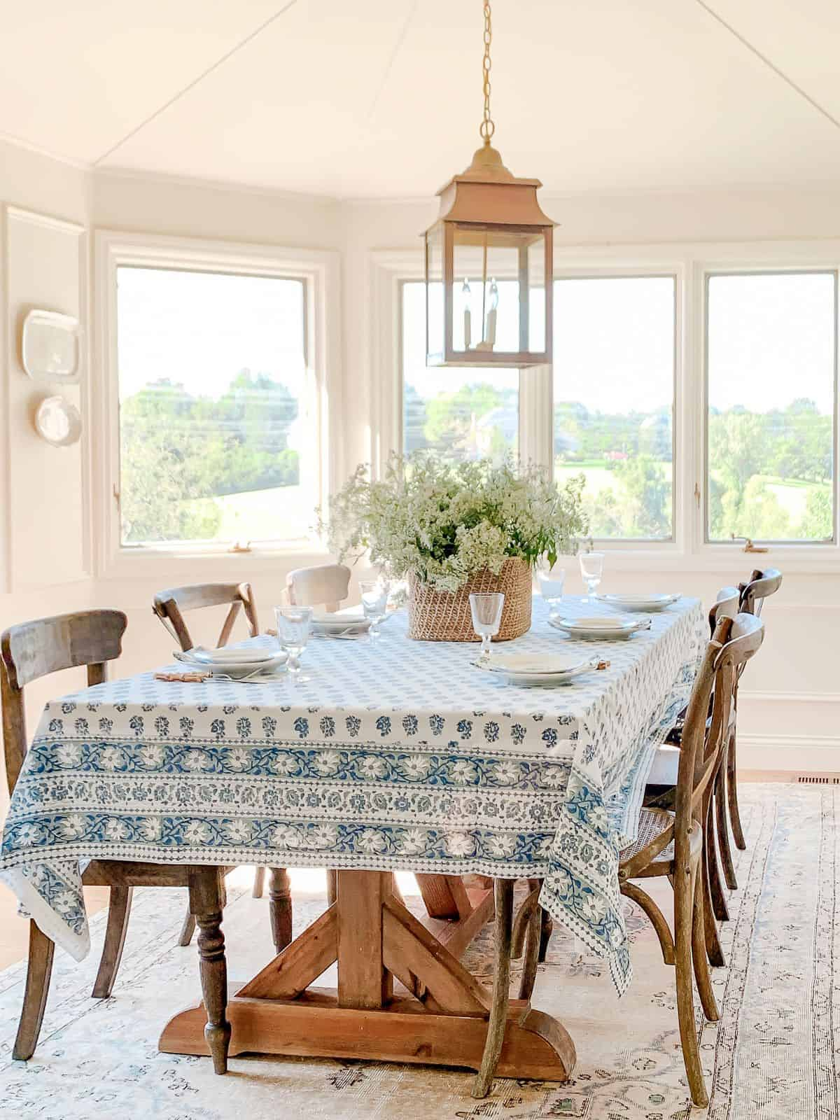 A white dining room with a brass lantern over the table, platters on the wall in the background.